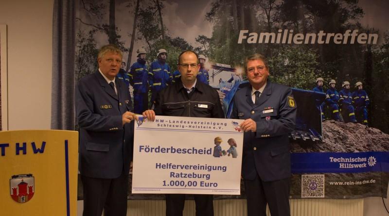 Eingerahmt durch den Ortsbeauftragten Andreas Timmermann (links) und dem Vorsitzenden des Helfervereinigung Torsten Schröder (rechts) übergibt der Landesschatzmeister Oliver Scharf den symbolischen Förderbescheid