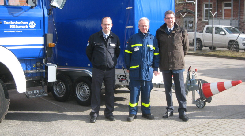 Der Vorsitzenden der HV Lübeck Andreas Mellmann (Mitte) präsentiert dem Vorsitzenden des Landesvereinigung SH Burkhard Hamm (rechts) und dem Landesschatzmeister Oliver Scharf (links) den neu gekauften Anhänger.